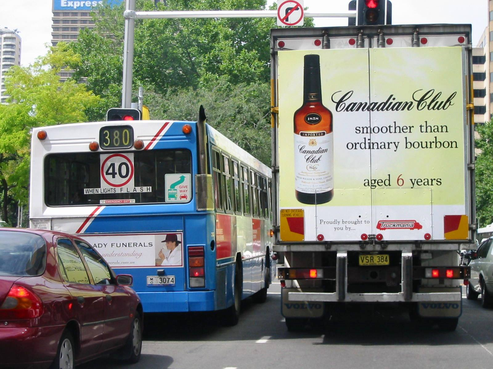 Truck advertising. TruckSide advertising. Fleet graphics. Vehicle Wraps. Canadian Club (CC) A Smooth Character Takes Time/Smoother Than Ordinary Bourbon campaign. Full TrackBack. Rigid tautliner.York Street Sydney southbound. Adjacent partially obscured bus back.