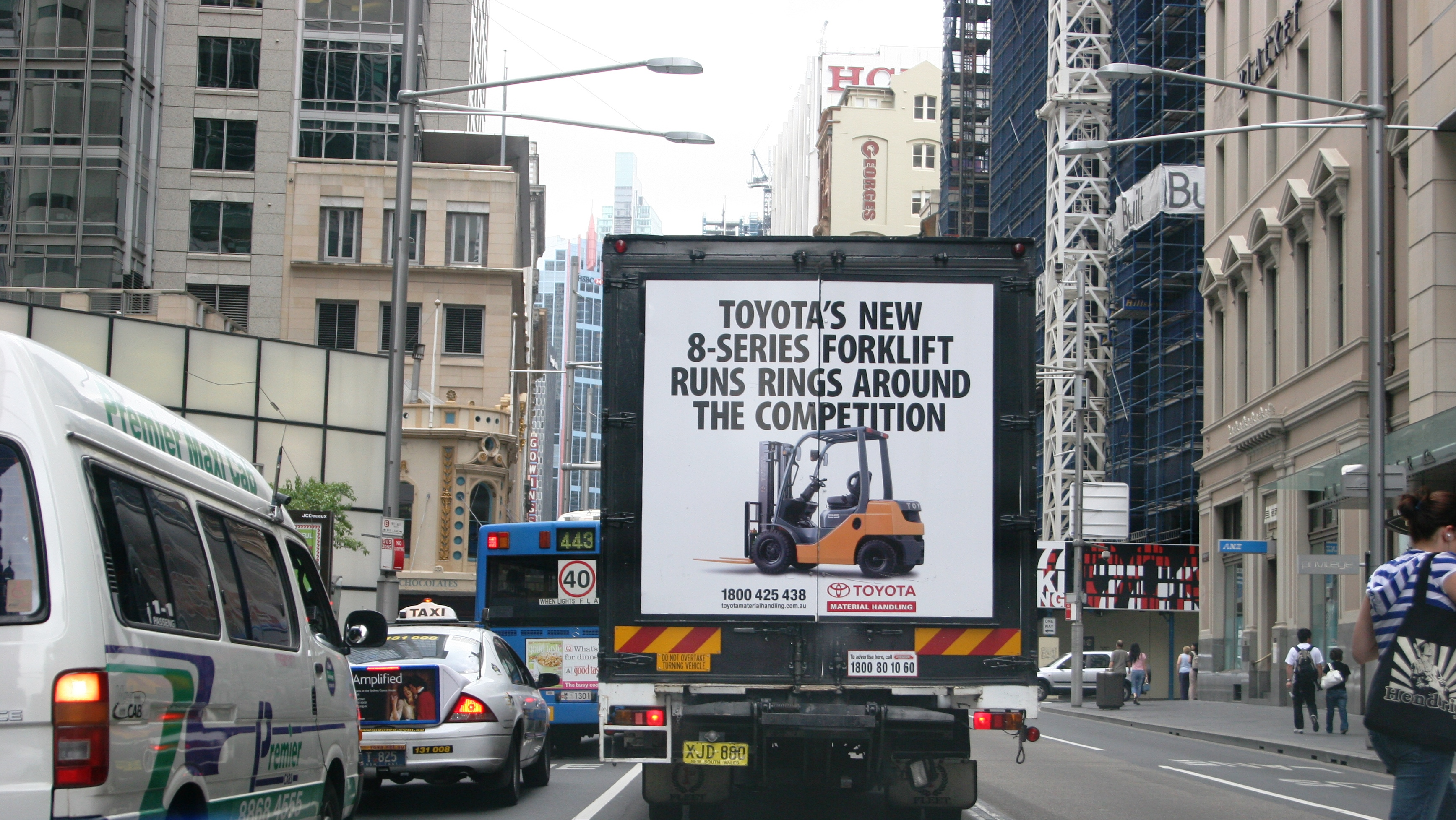 Truck advertising. TMHA Toyota Material Handling Australia TruckBack on First Fleet rigid. Frame. 8 series forklift Runs Rings Around the Competition campaign. Sydney Harbour Bridge at northern pylons southbound. Adjacent 4WD.