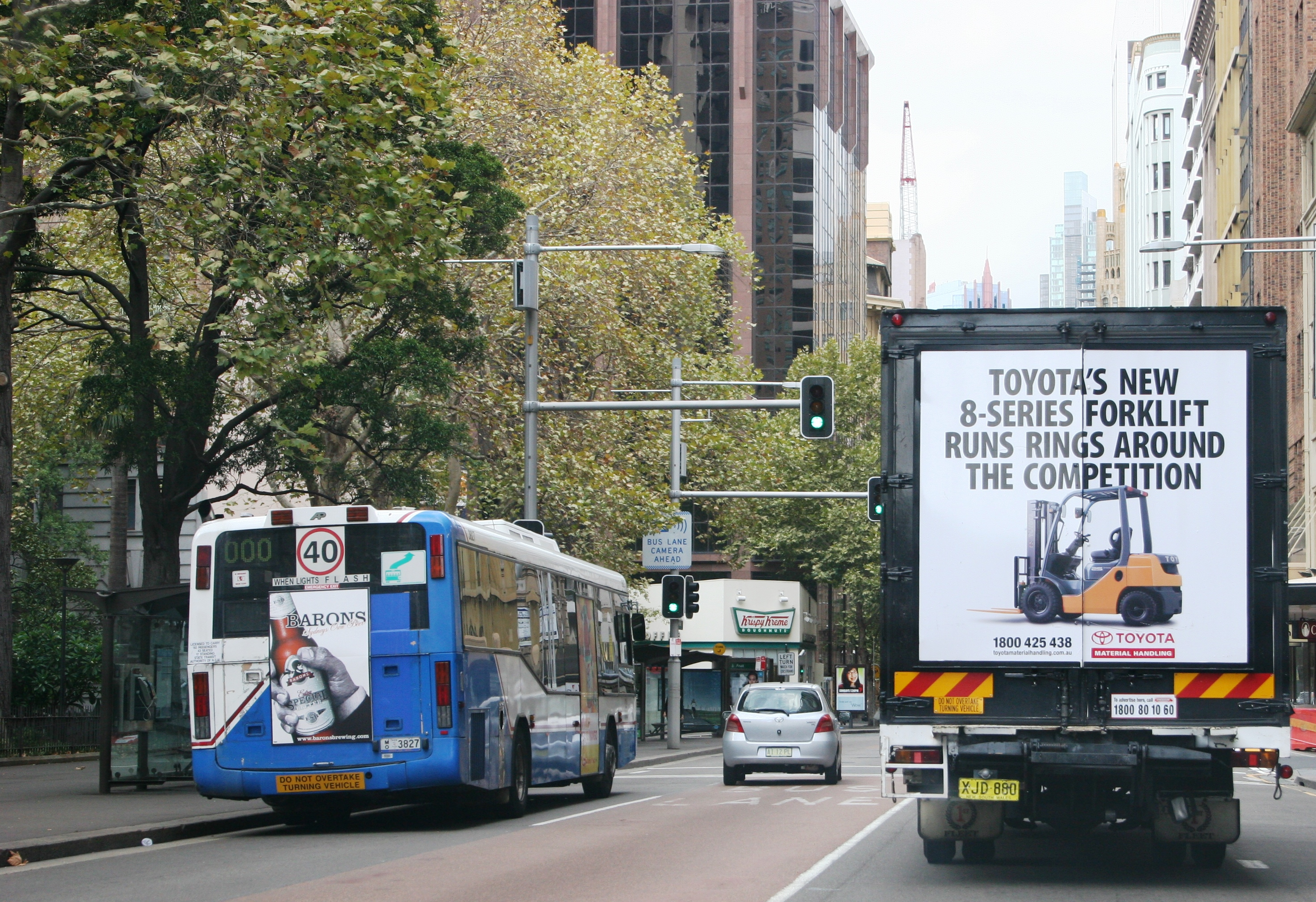 Truck advertising. TMHA Toyota Material Handling Australia TruckBack on First Fleet rigid. Frame. 8 series forklift Runs Rings Around the Competition campaign. York Street Sydney southbound. Adjacent to a bus back.