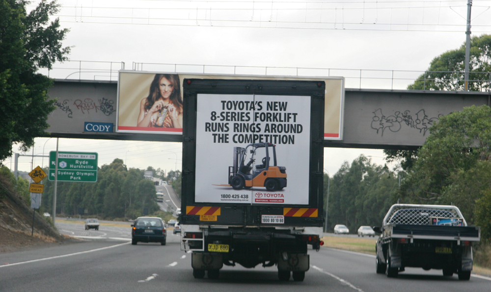 Truck advertising. TMHA Toyota Material Handling Australia TruckBack on First Fleet rigid. Frame. 8 series forklift. Homebush Bay Sydney eastbound near Olympic Park exit. Obscuring overhead billboard.