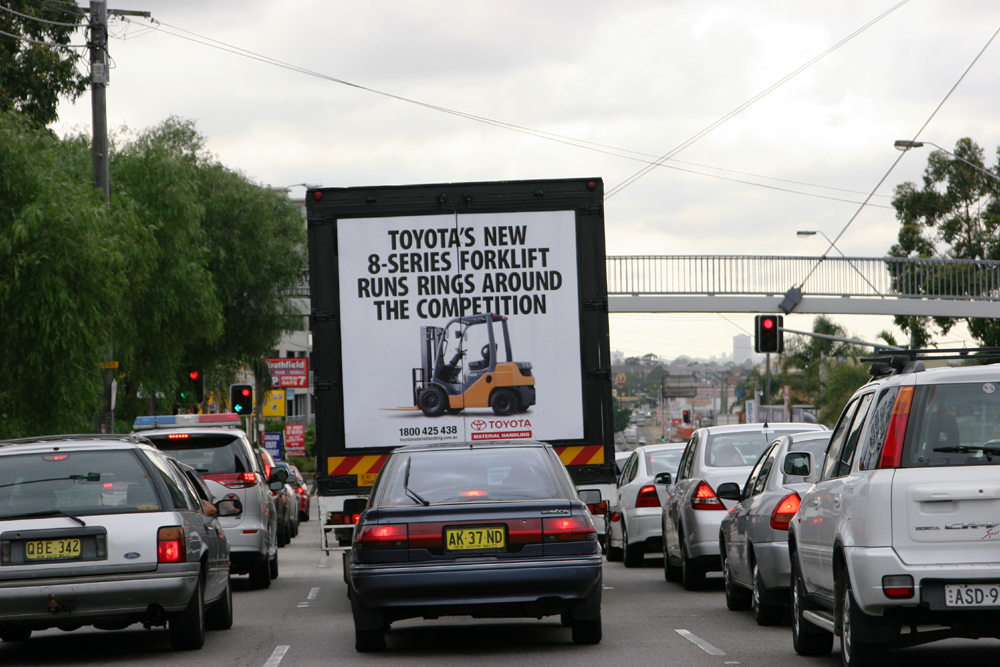 Truck advertising. TMHA Toyota Material Handling Australia TruckBack on First Fleet rigid. Frame. 8 series forklift. Parramatta Road Burwood, eastbound. In heavy traffic above other vehicles.