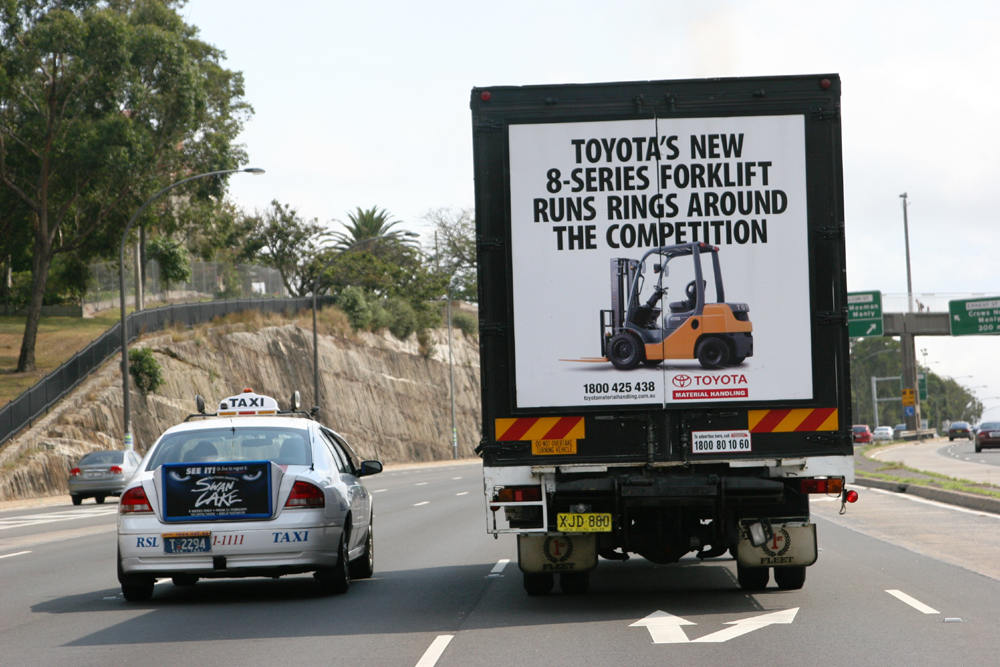 Truck advertising. TMHA Toyota Material Handling Australia TruckBack on First Fleet rigid. Frame. 8 series forklift. Warringah Expressway northbound. Adjacent to a taxi back.